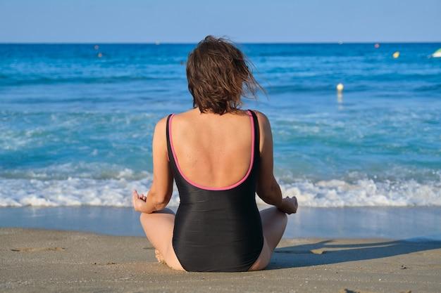 Stile di vita sano, sport, yoga, meditazione nelle persone mature. vista posteriore della donna di mezza età in costume da bagno che si siede sulla riva nella posizione del loto, sfondo tramonto mare cielo blu