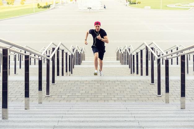 Stile di vita sano - giovane sportivo che corre al piano di sopra all'aperto