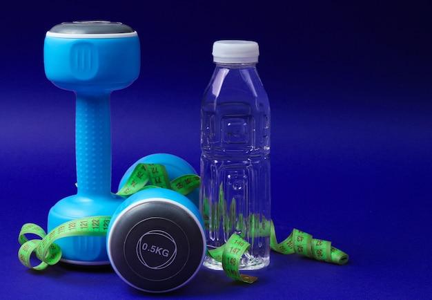 Stile di vita sano ancora in vita. manubri, righello, bottiglia d'acqua sull'azzurro