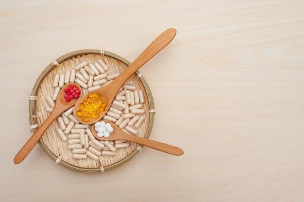 Stile di vita sano vitamine minerali e integratori alimentari in cucchiai di legno all'interno di un piatto di bambù intrecciato isolato su sfondo di legno vista dall'alto copia spazio