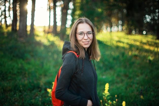 Donna di stile di vita sano che cammina nelle montagne nella zona della foresta di estate