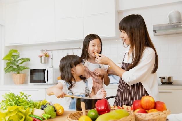 Bambina in buona salute che mangia frutta e gioca a cucinare con la mamma a casa cucina