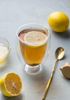 Tè al miele di limone e tè alle erbe di vita sana con radice di zenzero su una superficie grigia