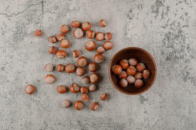 Noci di macadamia sane in guscio su una superficie di pietra.