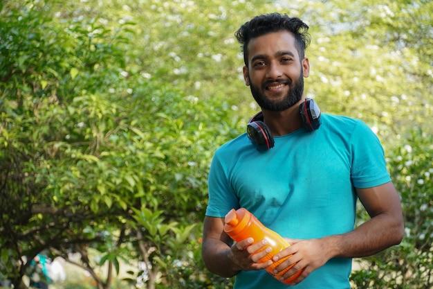 Uomo sano con bevanda proteica nello shaker al parco al mattino