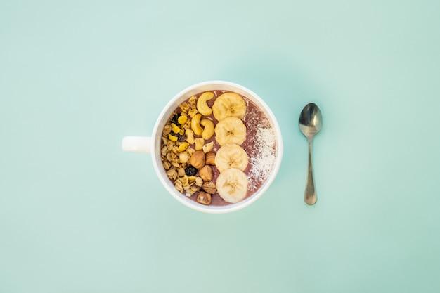 Concetto di pasto sano: una ciotola di frullato di frutta con noci e fette di banana. ciotola acai con cereali, anacardi e nocciole