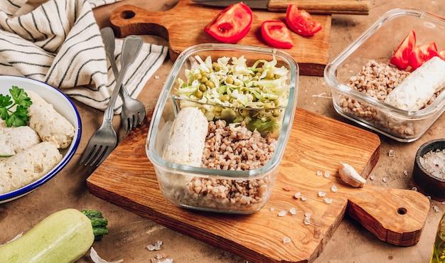 Contenitori per la preparazione di pasti sani con salsicce di pollo fatte in casa, grano saraceno e insalata di verdure su fondo rustico. dieta, concetto di perdita di peso. messa a fuoco selettiva
