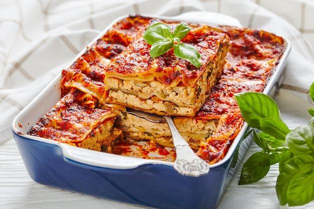 Lasagne al tofu vegane senza carne e senza latticini con funghi champignon, salsa di pomodoro, condimento italiano, servite su una teglia con erbe fresche su un tavolo di legno bianco, primo piano