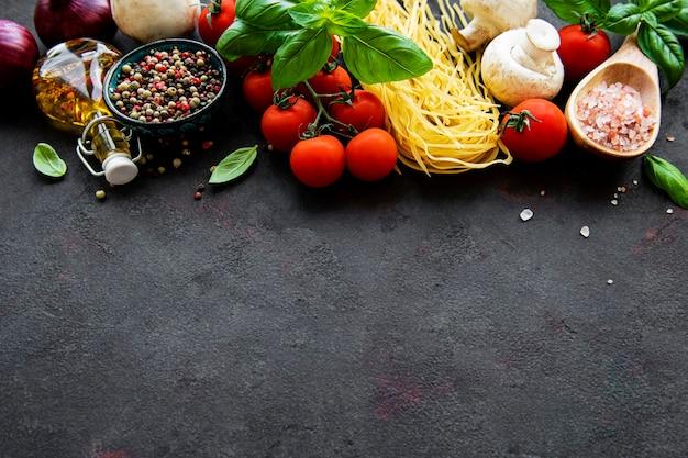 Una sana dieta mediterranea, ingredienti per il pasto italiano, spaghetti, pomodori, basilico, olio d'oliva, aglio, peperoni sulla superficie nera