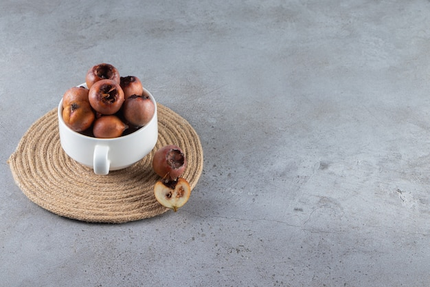 Frutti di nespola sani in una ciotola bianca posta su sfondo di pietra.