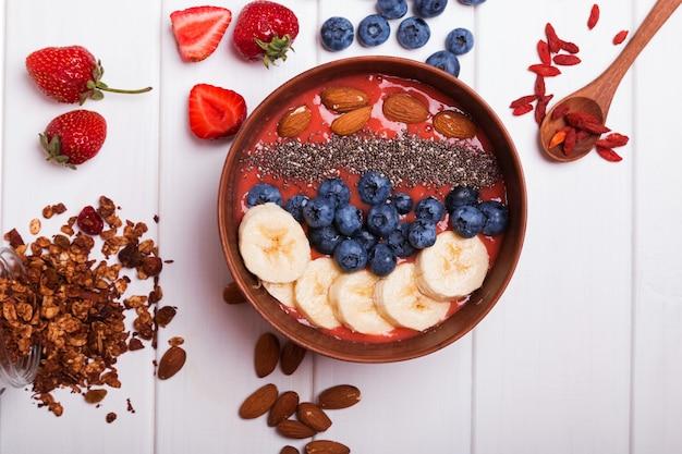 Sana colazione moderna. ciotola di frullato di fragole con noci e frutti di bosco