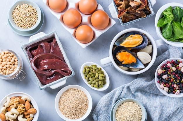 Concetto di dieta sana alimentazione. assortimento di cibi ricchi di ferro. fegato di manzo, spinaci, uova, legumi, noci, funghi, quinoa, sesamo, semi di zucca, fagioli di soia, frutti di mare. lay piatto