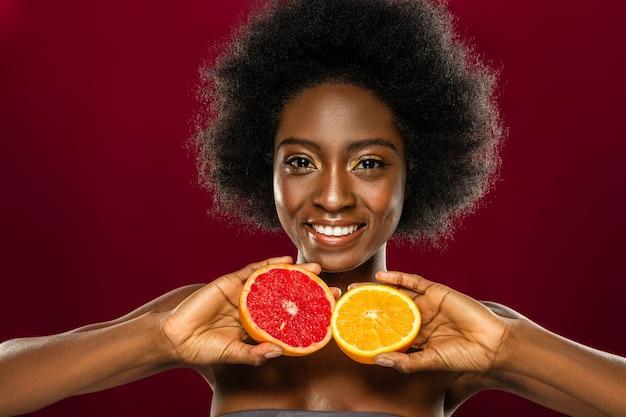 Alimentazione sana. donna abbastanza piacevole che mangia frutta fresca mentre conduce uno stile di vita sano