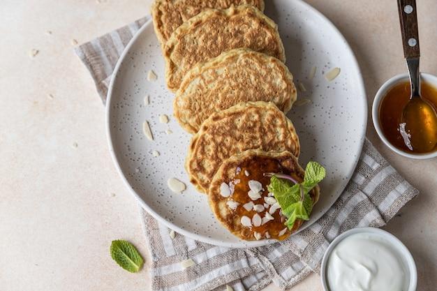 Pancakes di avena sani con noci di marmellata e menta su piatto di ceramica cibo vegano per la colazione