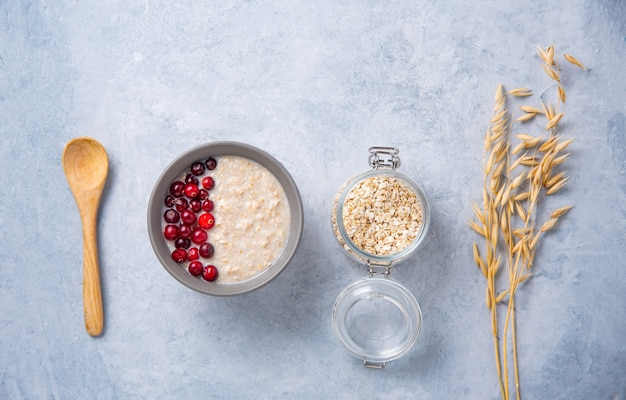 Porridge di avena sano con mirtilli rossi su sfondo azzurro con fiocchi di vaso e orecchie di farina d'avena. cibo dietetico per la colazione sana. vista dall'alto, piatto laici e copia il concetto di spazio