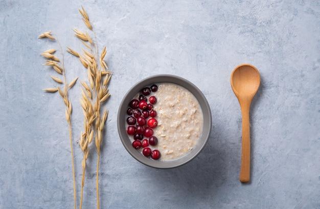 Porridge di avena sano con mirtilli rossi su sfondo azzurro con orecchie di farina d'avena e cucchiaio di legno