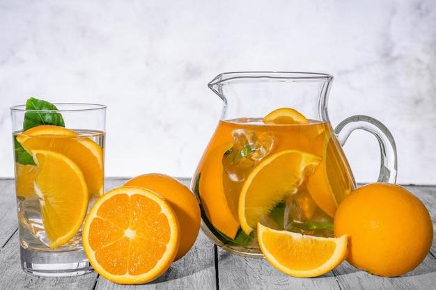 Sano detox arancia con arancia fresca e calce, in vetro sulla parete in legno.