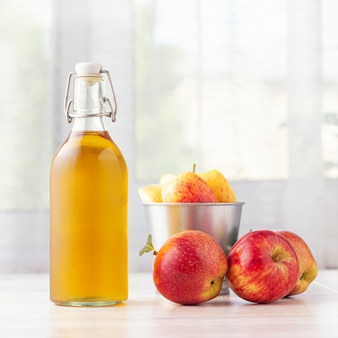 Alimenti biologici sani aceto di mele o succo di frutta in bottiglia di vetro e mele rosse fresche su uno sfondo chiaro.