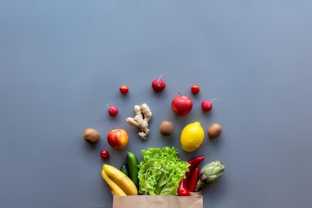 Cibo sano e biologico flay lay concept. borsa ecologica con foglie di insalata di lattuga, mele, kiwi, pomodoro, ravanello, limone, cetriolo, carciofo, peperone rosso e giallo e radice di zenzero.