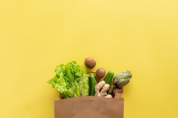 Cibo sano e biologico flay lay concept. borsa ecologica con foglie di insalata di lattuga, kiwi, cetriolo, carciofo e radice di zenzero.