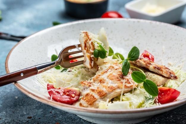Insalata caesar di pollo alla griglia biologica sana con formaggio, uova di quaglia e pomodorini, con salsa. menu del ristorante, dieta, ricetta del libro di cucina.