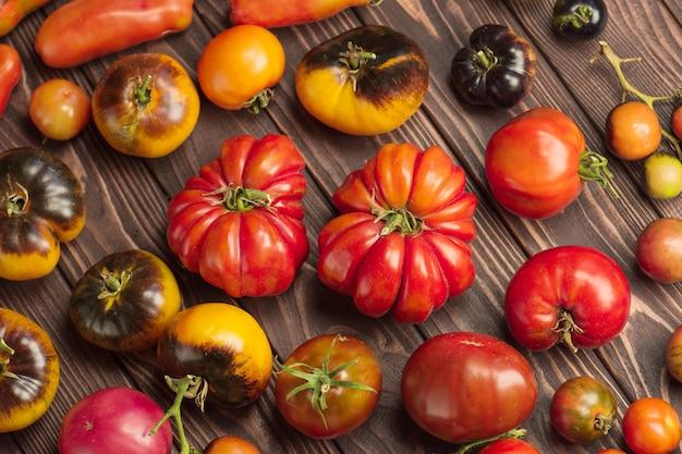 Pomodori organici sani su un fondo di legno. pomodori assortiti su fondo di legno rustico.