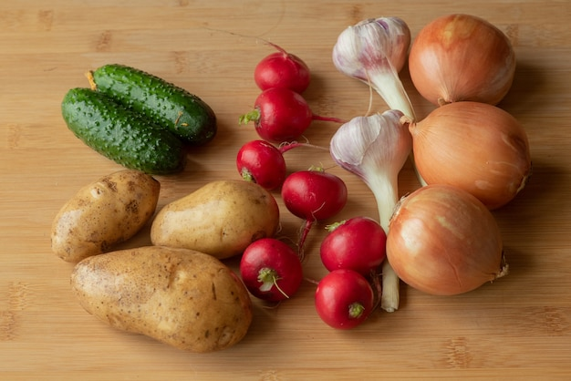 Ortaggi biologici sani su un tavolo di legno. aglio cipolla ravanello cetriolo patate su un tavolo di legno