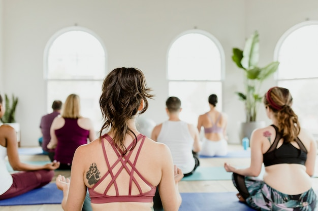 Persone sane che fanno una posa yoga sukhasana in una lezione di yaga