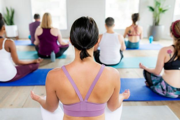 Persone sane che fanno una posa yoga sukhasana durante una lezione di yoga