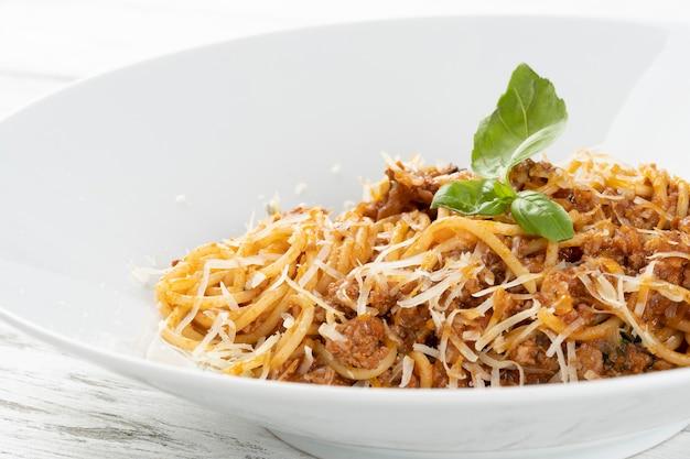 Piatto sano di spaghetti italiani conditi con un gustoso pomodoro e carne macinata salsa bolognese e basilico fresco su un rustico tavolo di legno bianco