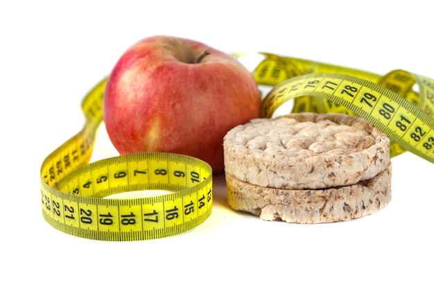 Galette di mais soffiato sano e mela rossa con nastro di misurazione su sfondo bianco.