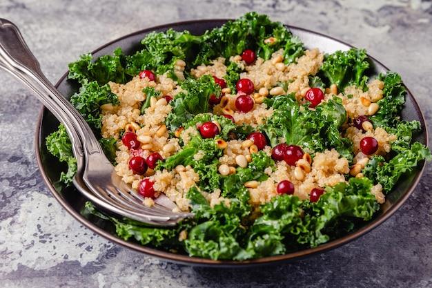 Insalata di cavolo crudo sano e quinoa con mirtillo rosso e pinoli. messa a fuoco selettiva.