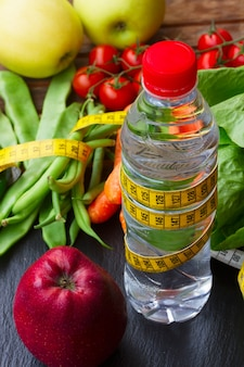Vegetablea crudo sano e friuts con bottiglia d'acqua sul tavolo