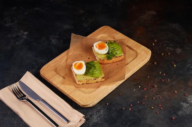 Pane tostato sano di segale con avocado, uova, formaggio feta sulla piastra