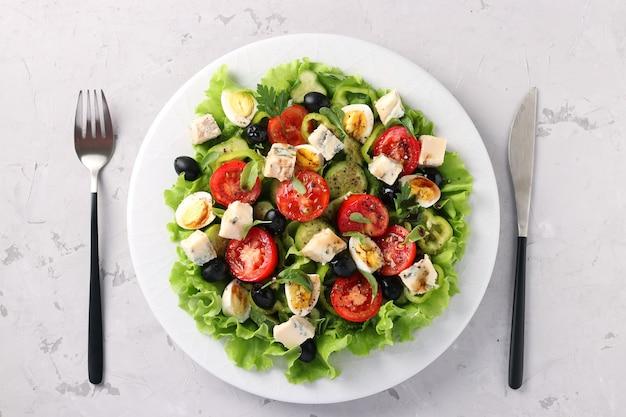 Una sana insalata di pomodorini, cetrioli, peperoni, olive nere, con olio d'oliva, uova di quaglia e gorgonzolla su una superficie leggera, vista dall'alto