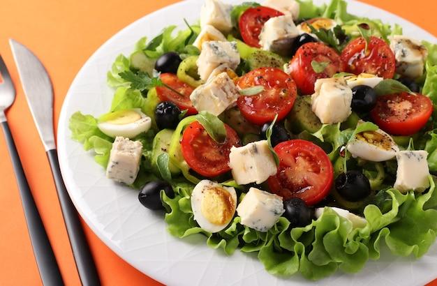 Una sana insalata di pomodorini, cetrioli, peperoni, olive nere, con olio d'oliva, uova di quaglia e gorgonzolla su una superficie arancione. avvicinamento
