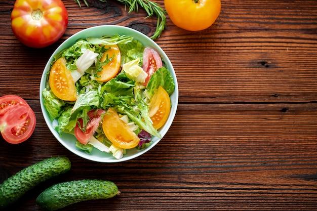Insalata sana di verdure fresche, erbe e pomodori su uno sfondo di legno. posto per il tuo testo.