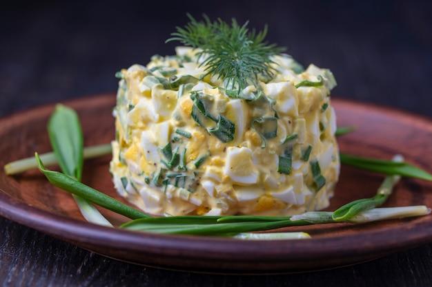 Una sana insalata di porro selvatico verde, uovo in camicia e panna acida su sfondo nero
