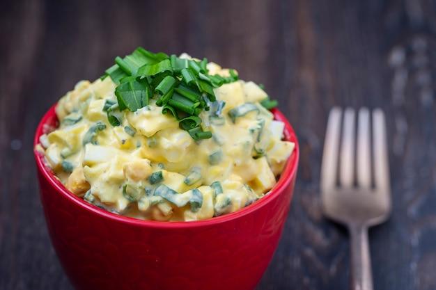 Una sana insalata di porro selvatico verde, uovo in camicia e panna acida in una ciotola rossa, da vicino
