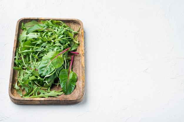 Insalata sana, insalata mista di foglie rucola, set di bietole, su sfondo di pietra bianca, con copia spazio per il testo