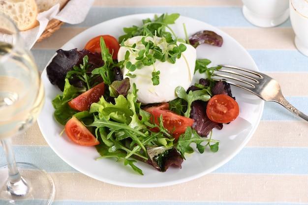 Una sana insalata a base di foglie di lattuga, verdure miste, porzioni di rucola, pomodori