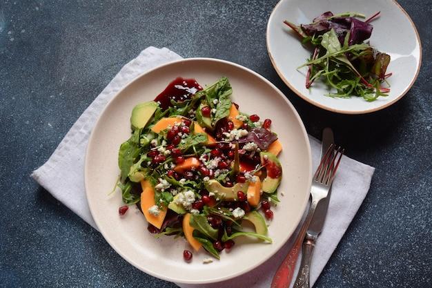 Insalata sana cachi, formaggio blu, spinaci, rucola, foglie di lattuga su piatto bianco