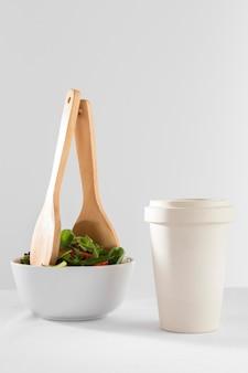 Una sana insalata in una ciotola bianca con una tazza di caffè