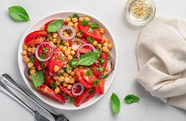 Insalata sana con ceci, pomodori ed erbe fresche su sfondo grigio. cibo vegetariano. vista dall'alto.
