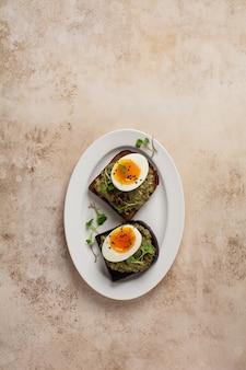 Panino sano con avocado, uova e microgreens su pane tostato su un piatto da portata per la colazione. concetto dietetico di nutrizione sana. vista dall'alto.