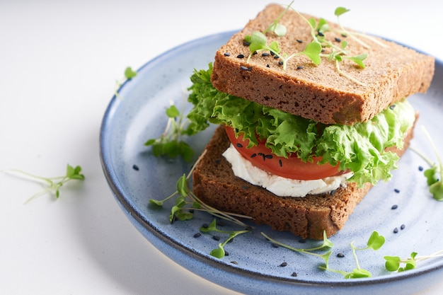Panino sano con pane senza glutine, pomodoro, lattuga e microgreens germinati, cosparsi di semi di sesamo serviti nel piatto