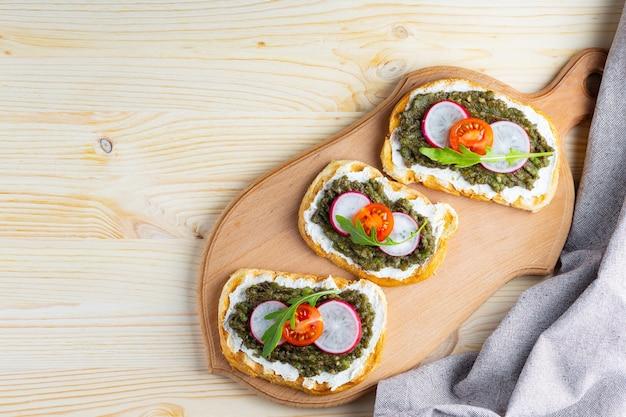 Panini sani con crema di formaggio, avocado, ravanello, pomodorini e rucola