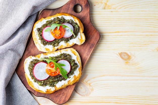 Panini sani con crema di formaggio, avocado, ravanello e pomodorini
