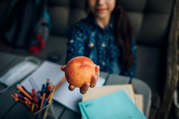 Sana colazione scolastica, pesca nelle mani di una studentessa. spuntino durante i compiti