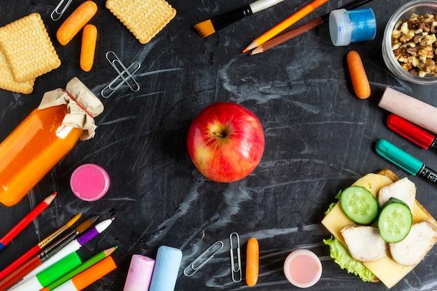 Concetto di pranzo scolastico sano. mela, panino, succo e cancelleria rossi sulla lavagna